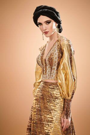 Femme de beauté orientale. Portrait d'une belle femme arabe en costume traditionnel, avec maquillage oriental traditionnel et hijab noir. Maquillage et cosmétiques.