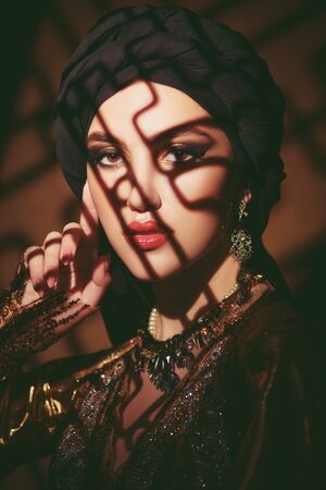 Oriental fairy tale. Portrait of a beautiful arab woman with traditional make-up and black hijab. Make-up and cosmetics. Standard-Bild