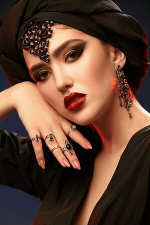 Arabian beauty, fashion. Portrait of a beautiful oriental woman with traditional make-up, black hijab and jewelry on a black background. Make-up and cosmetics.