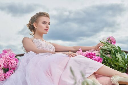 Portrait of a beautiful elegant young woman in a luxurious evening white dress sitting on a sofa with pink peony flowers against the blue sky. Beauty, fashion. Wedding style.