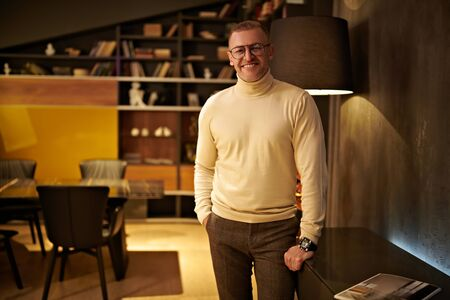 Handsome middle-aged businessman in elegant clothes and glasses stands in his office. Successful manager concept.