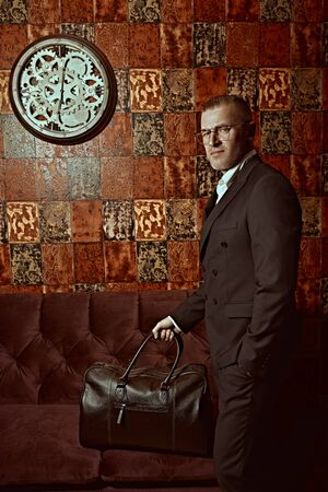 Portrait of a respectable middle-aged man in an elegant suit and glasses posing with luggage bag in a luxurious apartment. Success and rich lifestyle.