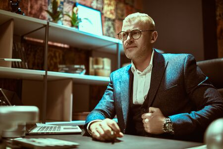 Respectable middle-aged businessman in a suit and glasses works in a modern office. Successful manager concept.