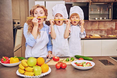 Happy family concept. Funny children and their mother make a mustache of spaghetti and cook dinner. Healthy eating.