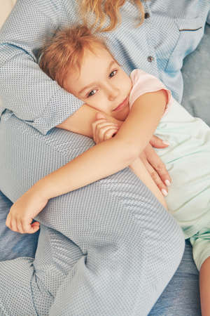 Little girl falls asleep in the bedroom in the arms of her mom. Happy family and love concept.