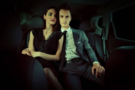 Fashionable couple of young people in the car. Glamorous lifestyle, night party.