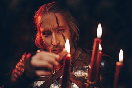 The witcher man in a wooden house by candlelight. Stage portrait. Medieval warrior in armor.  Imagens