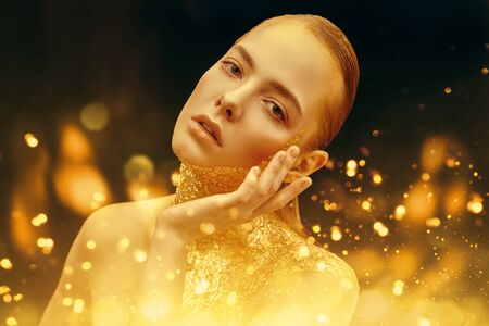 Beauty, fashion gold concept. Portrait of a beautiful girl model with golden skin and golden make-up on on a sparkling and black background with golden lights. Jewelry. Cosmetics and beauty care.