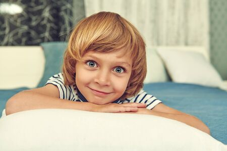 Joyful funny kid lying on a bed and smiling at camera. Happy childhood. Family at home.