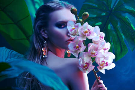 Beautiful tropical woman stands among tropical plants with orchid flowers. Beauty and fashion concept. Tropical vacation.