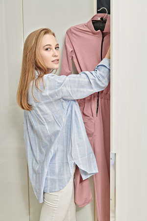 Beautiful young woman chooses clothes in her wardrobe at home. Home interior, furniture. Lifestyle.
