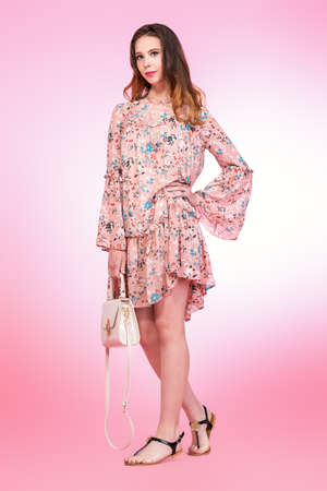 A full length portrait of a smiling romantic girl posing in the studio over the pink background. Summer casual fashion.