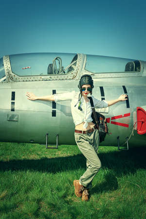 Portrait of a beautiful girl pilot posing in  helmet and sunglasses . Military aircraft.