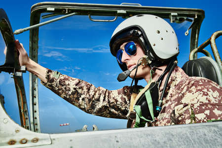 Portrait of a man pilot wearing helmet and sunglasses in cockpit of fighter jet. Military aircraft.
