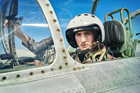 Portrait of a man pilot wearing helmet in cockpit of fighter jet. Military aircraft.