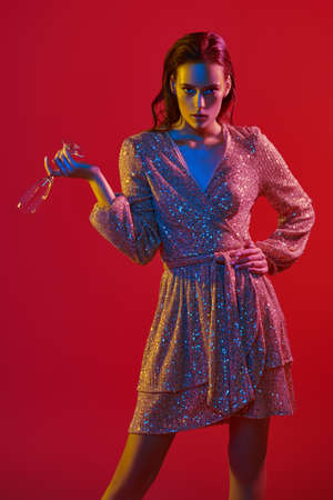 Make-up and cosmetics. Portrait of a gorgeous young woman with golden make-up posing with a champagne glass in a colored red, blue and yellow light. Party style.