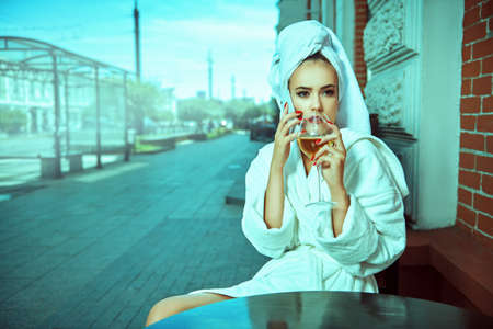 Glamorous young woman in a white terry dressing gown with a white towel on her head sits at a table in a street cafe with a glass of champagne and gossips on the phone. Fashion shot.