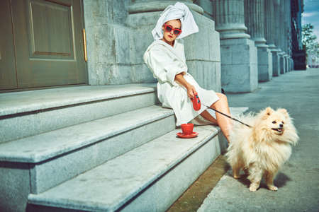 Extravagant lady in a white terry dressing gown with a white towel on her head and elegant sunglasses alluring on a city street with a cup of tea and her small fluffy dog. Beauty, fashion. Imagens
