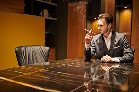Handsome brunet man in an elegant suit sits in a luxury apartment and smokes a cigar. Mafia. Male beauty, fashion.