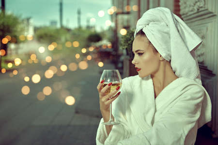 Glamorous young woman in a white terry dressing gown with a white towel on her head sits at a table in a street cafe with a glass of champagne. Fashion shot.