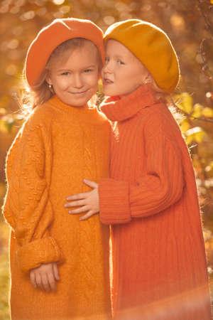 Autumn season. Two cute little girls walk through a beautiful autumn park. Retro style. Children's fashion.