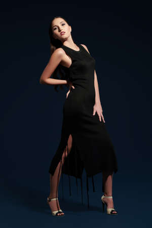 Fashion shot. Full length portrait of a gorgeous young woman in a tight black dress and in high-heeled shoes posing on a dark blue background.