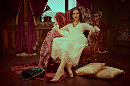 Bohemian lifestyle. Beautiful young woman in elegant lace dress and jewelry posing in a vintage armchair in a luxurious interior. Fashion shot, oriental style.