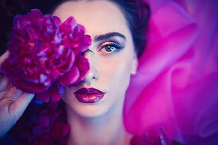 Beauty and flowers concept. Portrait of a magnificent brunette woman with bright make-up lying among peony flowers. Cosmetics, make-up. Perfumery.