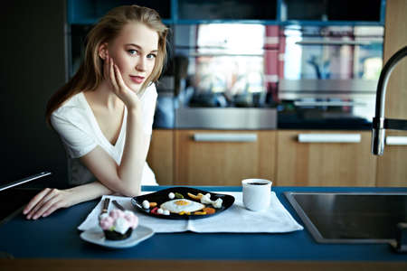 Cute blonde girl having a breakfast at home in the kitchen. Healthy eating and diet. Modern interior, furniture for the kitchen.