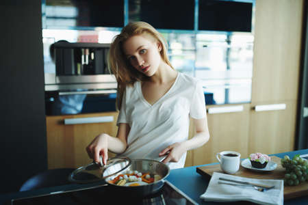 Cute blonde girl prepares breakfast at home in the kitchen. Healthy eating and diet. Modern interior, furniture for the kitchen.