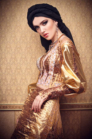 Oriental beauty woman. Portrait of a beautiful arabian woman in traditional dress, with traditional oriental make-up and black hijab. Make-up and cosmetics. Banque d'images