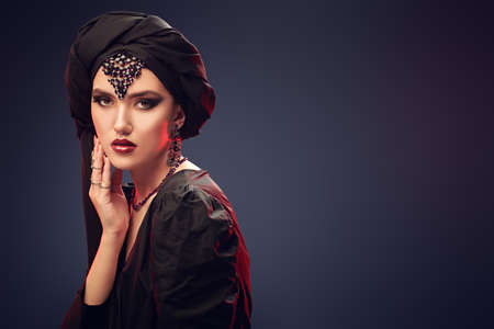 Arabian beauty, fashion. Portrait of a beautiful oriental woman with traditional make-up, black hijab and jewelry on a dark blue background. Make-up and cosmetics.
