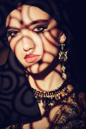 Oriental fairy tale. Portrait of a beautiful arab woman with traditional make-up and black hijab. Make-up and cosmetics. Zdjęcie Seryjne