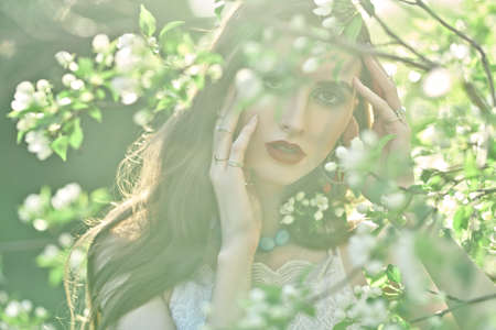 Portrait of a romantic brunette girl among the branches of a blossoming apple tree. Beauty of a spring. Make-up and cosmetics.