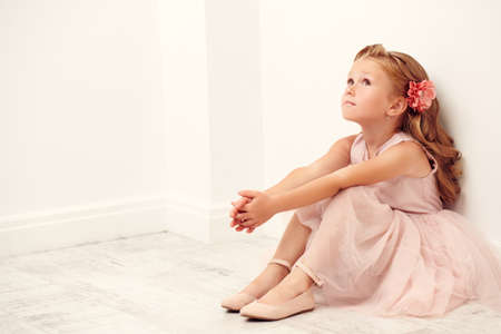 Portrait of a cute little girl sitting on the floor in a white room. Studio shot. Happy childhood.