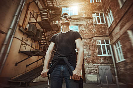 Handsome young man in casual clothes stands on the street in the old district of the city. Urban grunge style. Male fashion.