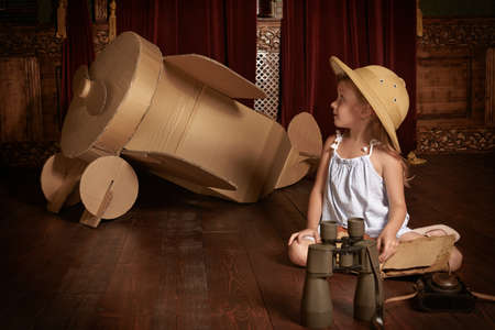 A little girl dressed as a traveler poses in a room with a cardboard model of an airplane. Childhood. Studio.