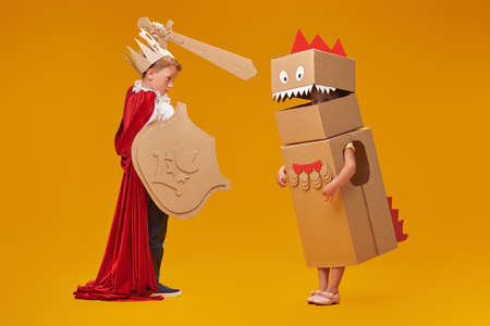 Portrait of a cute boy in costume of knight with cardboard armor is fighting the cardboard dragon. Childhood dreams. Full length portrait on a yellow background. Banque d'images