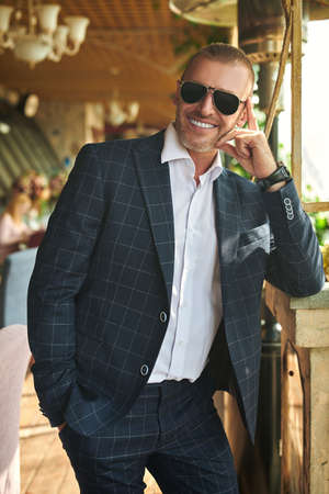 Handsome mature man in an elegant classic suit stands on the summer terrace. Male fashion. Optics, sunglasses for men. Summer vacation.