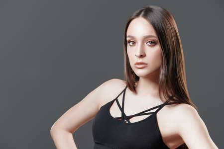 Attractive fashion model posing at studio in black clothes on a gray background. Beauty, fashion.