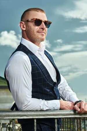 Happy handsome mature man in an elegant classic suit having a rest on the summer terrace. Men's fashion. Optics, sunglasses for men. Summer vacation. Reklamní fotografie