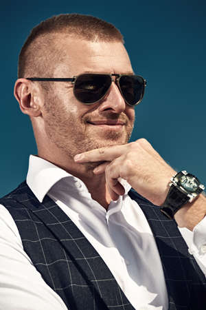 Portrait of a smiling handsome mature man in elegant classic suit and modern sunglasses against blue sky. Men's style. Optics for men.