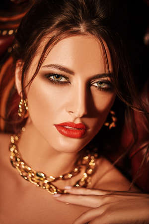Close up portrait of a stunning young woman with evening make-up and hairstyle wearing golden jewelry. Beauty, fashion.