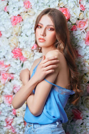 Spring and summer beauty. Portrait of a tender young woman with long wavy hair and colorful makeup on a background of roses. Make-up and cosmetics.