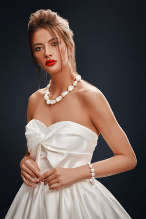 Portrait of a beautiful young bride woman in a fashionable white dress on a gray background. Wedding fashion. Make-up and hairstyle.
