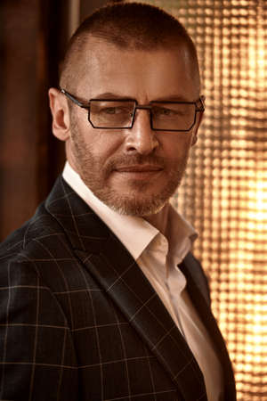 Close-up portrait of a smiling successful mature man in elegant suit and glasses. Male style. Optics for men.