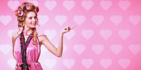 Pretty woman in pink lingerie and with curlers in her hair posing over pink background with hearts. Beauty, fashion concept. Pin-up style.