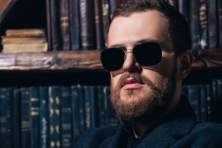 A close up portrait of a stylish man wearing sunglasses. Beauty and style for men.