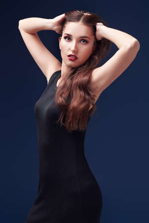 Fashion, beauty concept. Portrait of a gorgeous young woman in a tight black dress posing on a dark blue background.