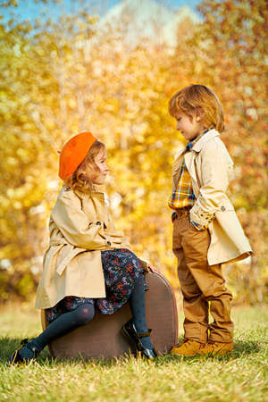 Happy romantic kids boy and girl posing with old fashioned suitcase in autumn park. Children's fashion. Retro style.
